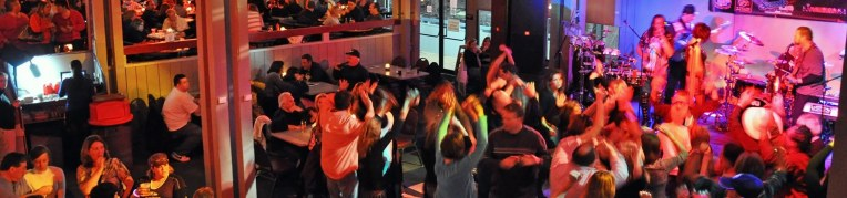 Group of people dancing with their hands in the air at Live at the Lodge party at Massanutten Resort