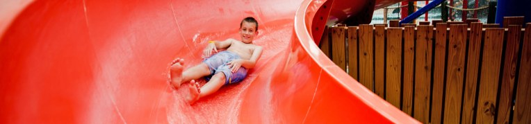 A boy going down a slide at Massanutten Indoor WaterPark