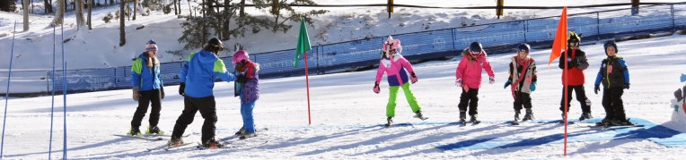 A ski and snowboard instructor teaches students how to ride on skis