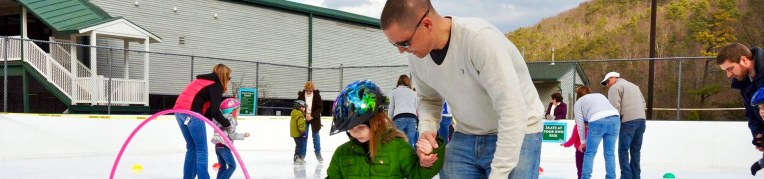 Father holding his daughters hand as they maneuver around the Massanutten Ice Skating Rink