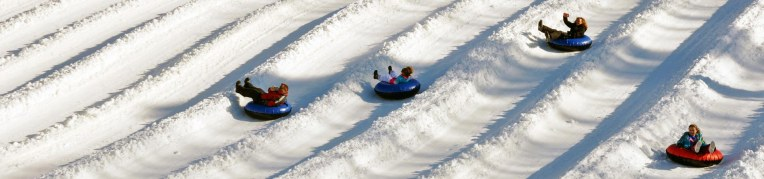 Four riders go down the snow tubing hill at that Snow Sports Adventure Park