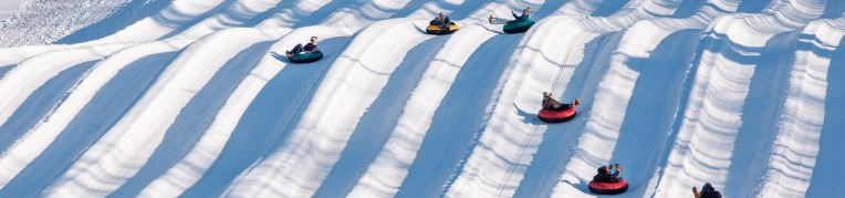 Six riders go down the snow tubing hill at Massanutten Resort