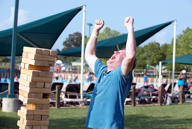 man shouting in victory during a game of jenga