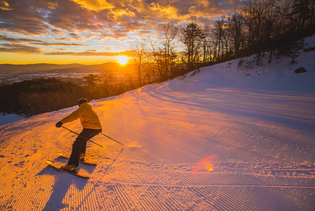 A skier carves at sunrise