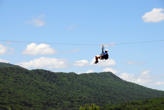 man on zipline in mountains